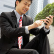 Chinese Businessman Dialling On Mobile Phone Outside Office — Stock Photo #24447577