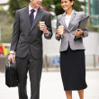 Businessman And Businesswoman Walking Along Street Holding Takea — Stock Photo