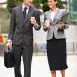 Businessman And Businesswoman Walking Along Street Holding Takea - Stock Photo
