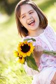 Giovane ragazza seduta in azienda di campo estivo girasole — Foto Stock