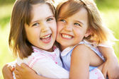 Two Young Girls Giving One Another Hug In Summer Field — Stock Photo