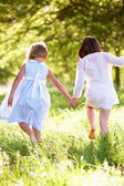 Two Young Girls Walking Through Summer Field Together — Stock Photo