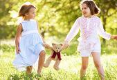 Dwie młode dziewczyny spaceru przez lato pole prowadzenie pluszowego misia — Zdjęcie stockowe