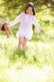 Young Girl Walking Through Summer Field Carrying Teddy Bear — Stock Photo