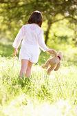 Młoda dziewczyna idąc przez lato pole prowadzenie pluszowego misia — Zdjęcie stockowe