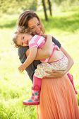 Mother Carrying Young Daughter Through Summer Field — Stock Photo