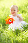 Baby Girl In Summer Dress Sitting In Field Holding Windmill — Stock Photo
