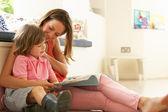 Matka siedzi z synem czytanie historia pomieszczeniu — Zdjęcie stockowe