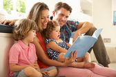 Parents Sitting With Children Reading Story Indoors — Stockfoto