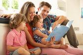 父母与孩子们读故事在室内坐 — 图库照片