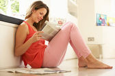 Woman Relaxing With Newspaper At Home — Stock Photo