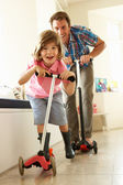Father And Son Riding Scooters Indoors — Stock Photo