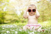 Baby Girl In Summer Dress Sitting In Field Wearing Sunglasses — Stock Photo