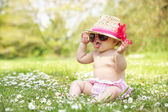Baby Girl In Summer Dress Sitting In Field Wearing Sunglasses An — Stock Photo