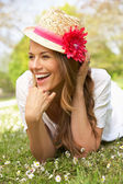 Woman Lying In Field Of Summer Flowers With Straw Hat — Stock Photo