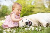 Dziewczynka w lato sukienka, siedząc w dziedzinie pieszczoty pies rodzinny — Zdjęcie stockowe