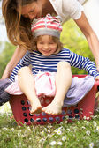 Mother Carrying Son Sitting In Laundry Basket — Stock Photo