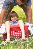 Padre portando il figlio seduto nel cesto della biancheria — Foto Stock