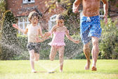 Father And Two Children Running Through Garden Sprinkler — Stock Photo