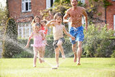 Family Running Through Garden Sprinkler — Stock Photo