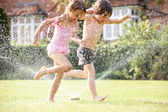 Two Children Running Through Garden Sprinkler — Stock Photo
