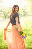 Vrouw lopen door zomer veld uitvoering boeket van bloemen — Stockfoto