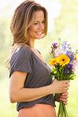 Donna che cammina attraverso il campo estivo che trasportano il mazzo di fiori — Foto Stock