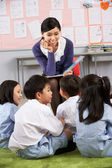 Teacher Reading To Students In Chinese School Classroom — Stock fotografie