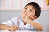 Männliche schüler arbeiten an schreibtisch in chinesische schule unterricht — Stockfoto