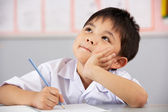 Uczeń pracuje przy biurku w klasie szkoły chiński — Zdjęcie stockowe