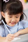 Vrouwelijke student werkt aan balie in chinese school klas — Stockfoto