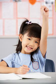 Female Student Working At Desk In Chinese School Classroom — Stock Photo