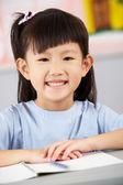 Studentessa che lavora al banco nell'aula di scuola cinese — Foto Stock