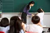 Male Pupil Writing On Blackboard In Chinese School Classroom — Stock Photo