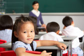 Portrait Of Female Pupil Working At Desk In Chinese School Class — Stock Photo