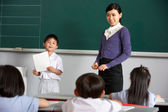 Pupil And Teacher Standing By Blackboard In Chinese School Class — Stock Photo