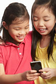 Studio Shot Of Two Chinese Girls With Mobile Phone — Stock Photo