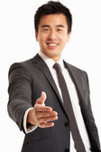 Studio Portrait Of Chinese Businessman Reaching Out To Shake Han — Stock Photo
