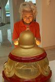 Mulher chinesa sênior rezando a estátua de buda em casa — Fotografia Stock