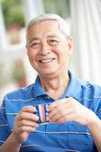 старший китайский человек пить чай на диване у себя дома — Стоковое фото