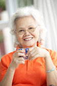 Senior Chinese Woman Drinking Tea On Sofa At Home — Stock Photo