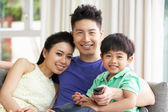 Chinese Family Sitting And Watching TV On Sofa Together — Stock Photo