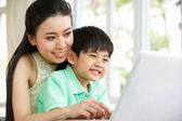 Chinese Mother And Son Sitting At Desk Using Laptop At Home — Stock Photo