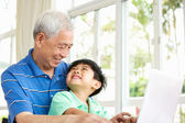Chinese Grandfather And Grandson Sitting At Desk Using Laptop At — Foto Stock