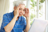 Worried Senior Chinese Man Sitting At Desk Using Laptop At Home — Stock Photo