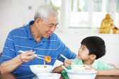 Portrait Of Chinese Grandfather And Grandson Eating Meal Togethe — Stock Photo