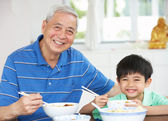 Portrait Of Chinese Grandfather And Grandson Eating Meal Togethe — Foto Stock