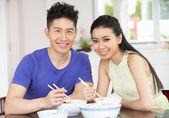 Pareja joven chino sentado en casa comiendo — Foto de Stock