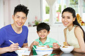 Chinese Family Sitting At Home Eating A Meal — Stock Photo