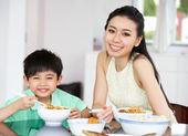 Chinese Mother And Son Sitting At Home Eating A Meal — Stock Photo